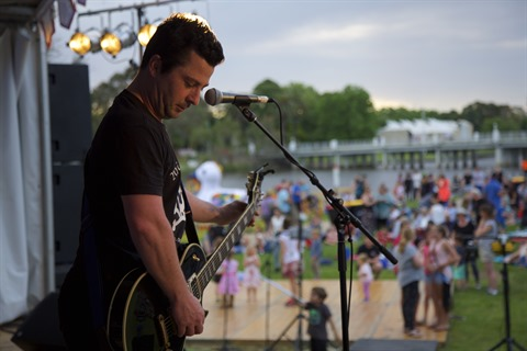Man playing guitar on stage to Benalla Festival crowd.jpg