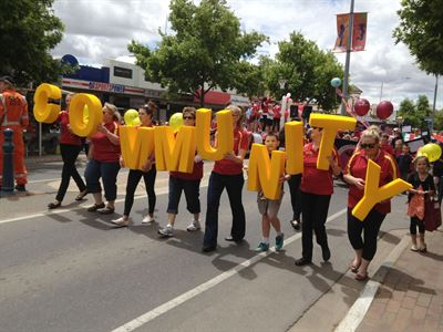 People at the Bridge St Fiesta Parade holding letters that spell out Community