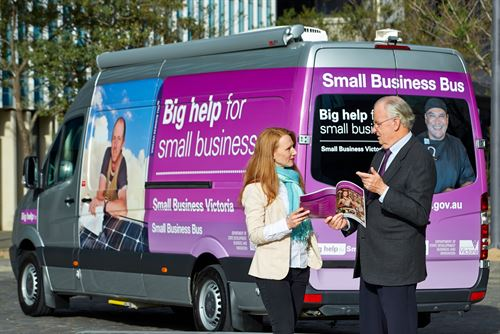 Image of woman talking to man and looking at booklet in front of small business bus
