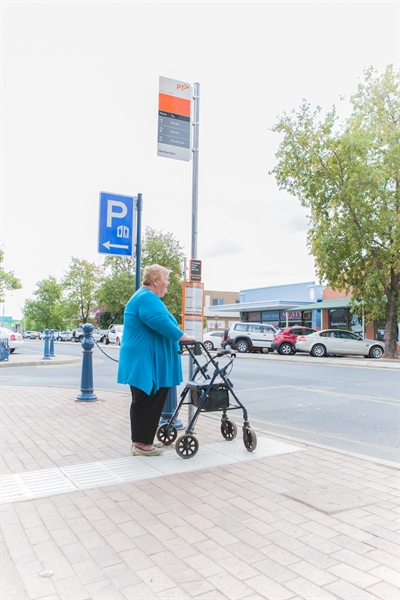 Woman with walker at bus stop